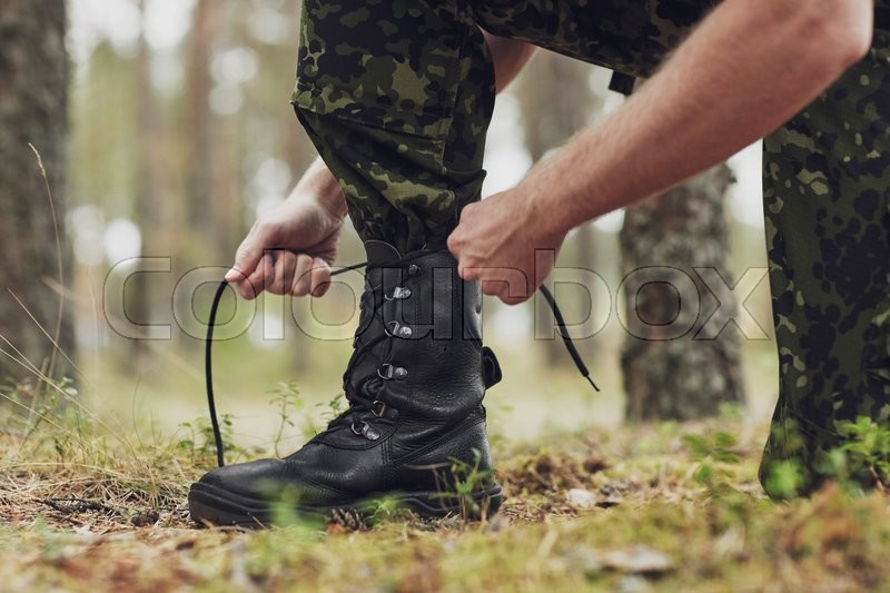 War, hiking, army and people concept - close up of soldier boots and hands tying bootlaces in forest, stock photo