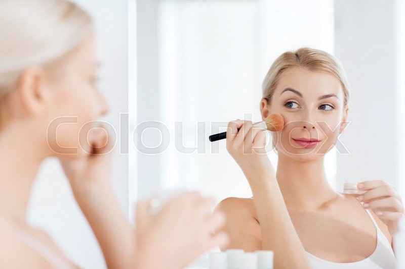Beauty, make up, cosmetics, morning and people concept - young woman makeup brush and powder foundation looking to mirror at home bathroom, stock photo