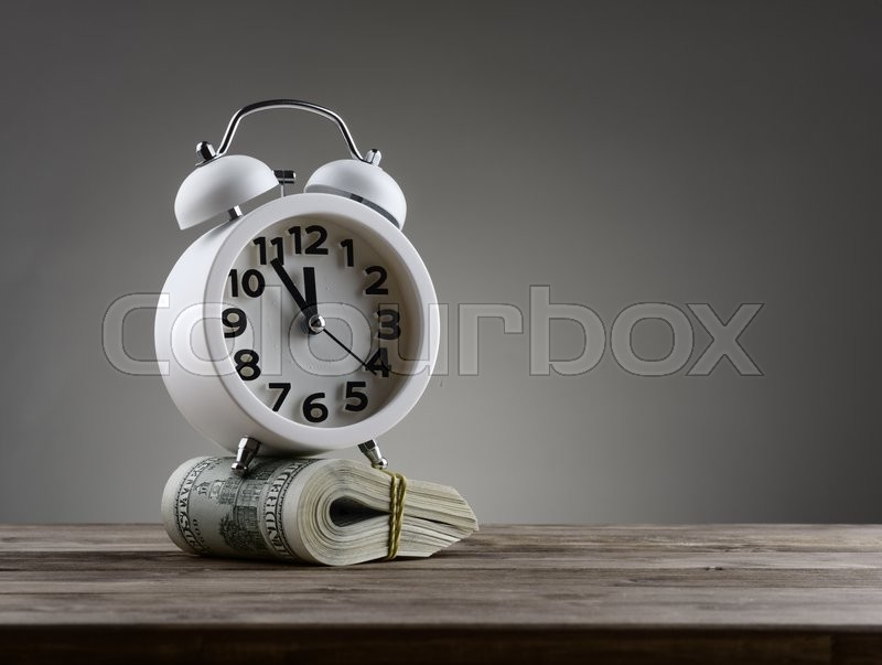 Time is money concept with clock and dollars, stock photo