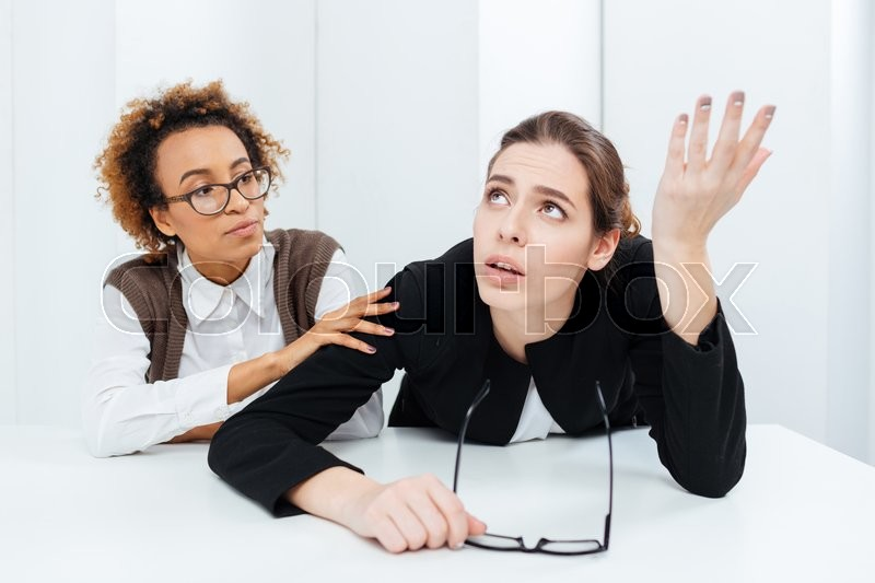 Pretty african american young businesswoman in glasses sitting and supporting her upset despaired colleague in office, stock photo