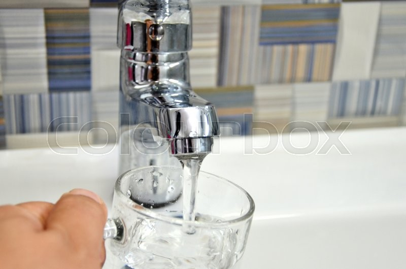 Filling glass of water from stainless steel kitchen faucet, stock photo