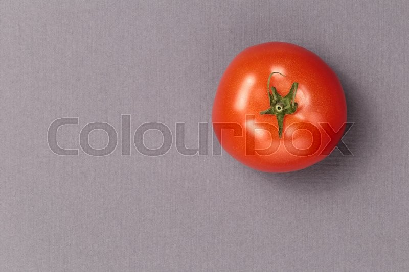 Top view of a red juicy tomato on a grey background. Bright and juicy tomato in the top right corner of the image. Tasty tomato. Tomato wallpaper. Tomato menu. Vegetable texture, stock photo