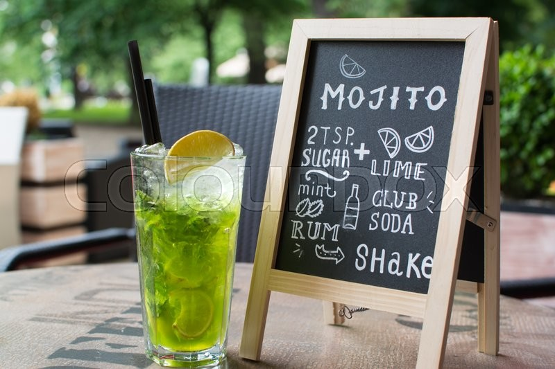 Hand drawn cocktails doodles. Mojito Chalk lettering. A variety of hand-drawn text and illustrations to compose the Mojito cocktail recipe. Mojito cocktail and recipe on the blackboard, stock photo