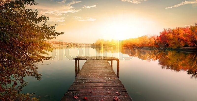 Red autumn and wooden fishing pier on river, stock photo