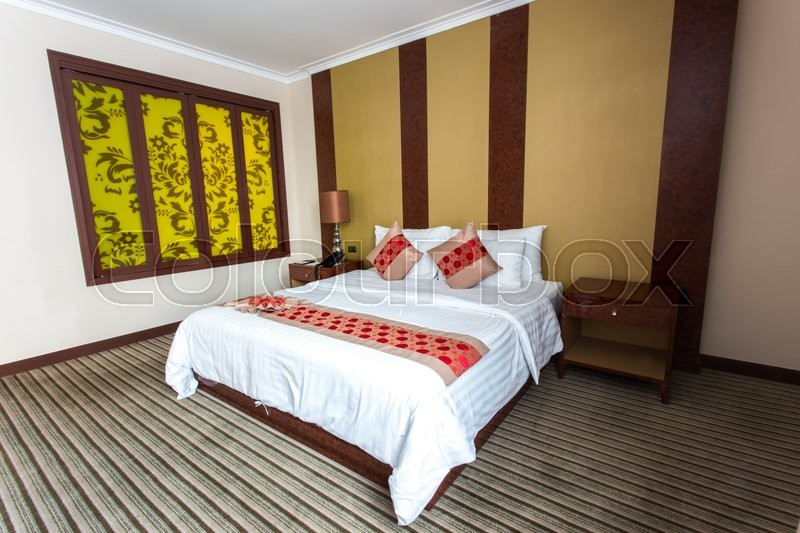 White bed in empty bedroom with yellow window on wall, stock photo