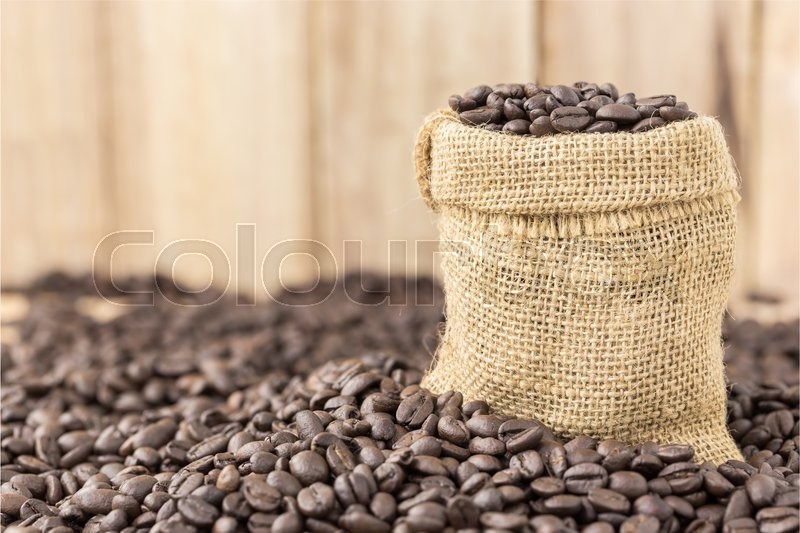 Coffee beans in bag on roasted coffee seed and wooden background, stock photo