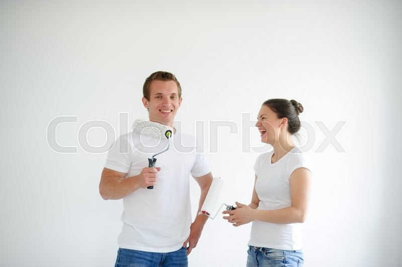 Boy and girl holding hands in the rollers. They rejoice in the end of the repair. Behind them, a white wall, stock photo
