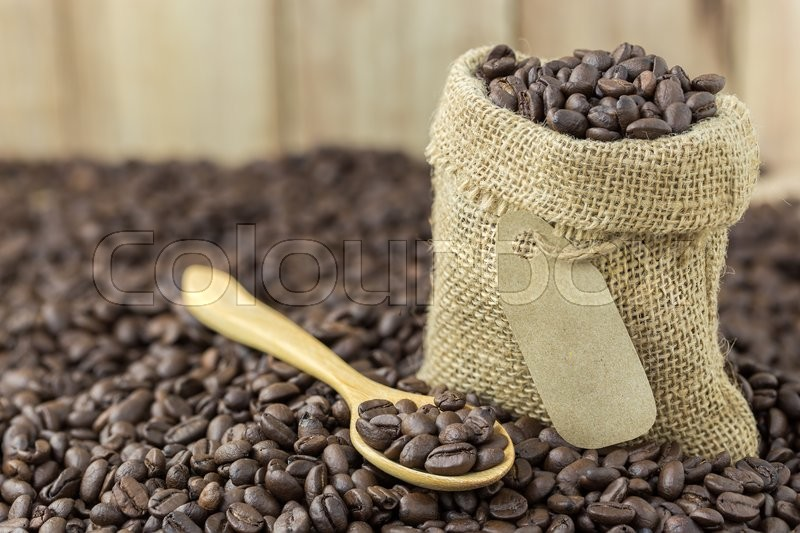 Coffee beans in sack bag and spoon on roasted coffee seed background, stock photo