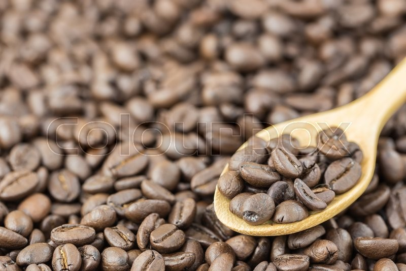 Coffee beans in spoon on roasted coffee seed background , stock photo