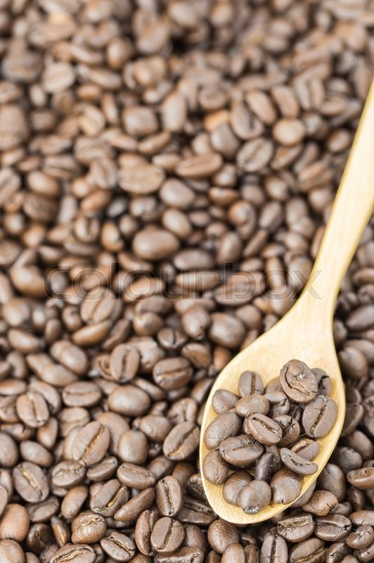 Coffee beans in spoon on roasted coffee seed background\\ , stock photo