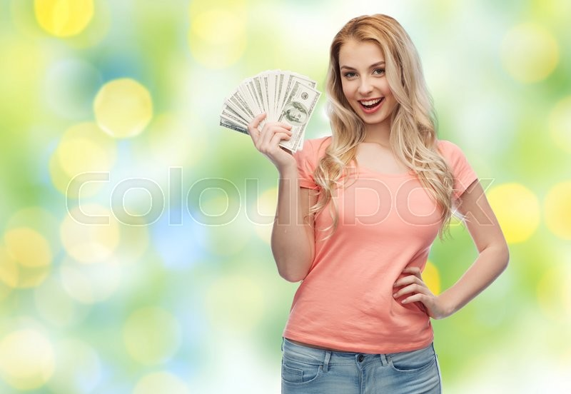 Money, finances, investment, saving and people concept - happy young woman with dollar cash money over summer green lights background, stock photo