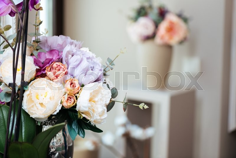 Bouquets of beautiful flowers standing in vases in the room, stock photo