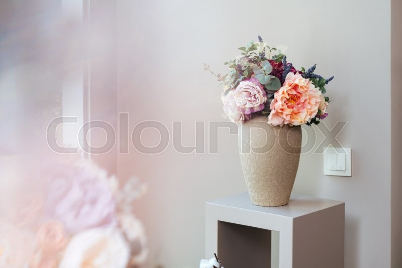 Vase with beautiful fresh flowers standing on small table , stock photo