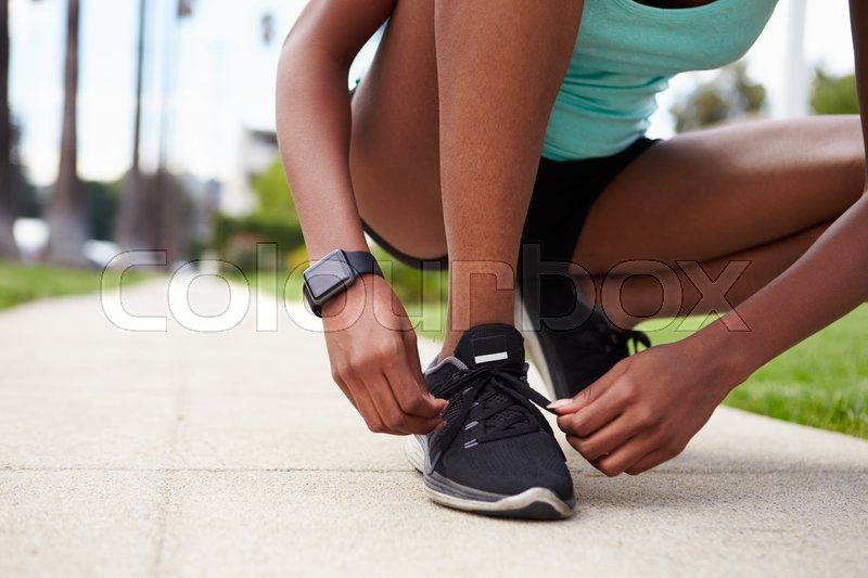 Young black woman tying sports shoes in the street, stock photo