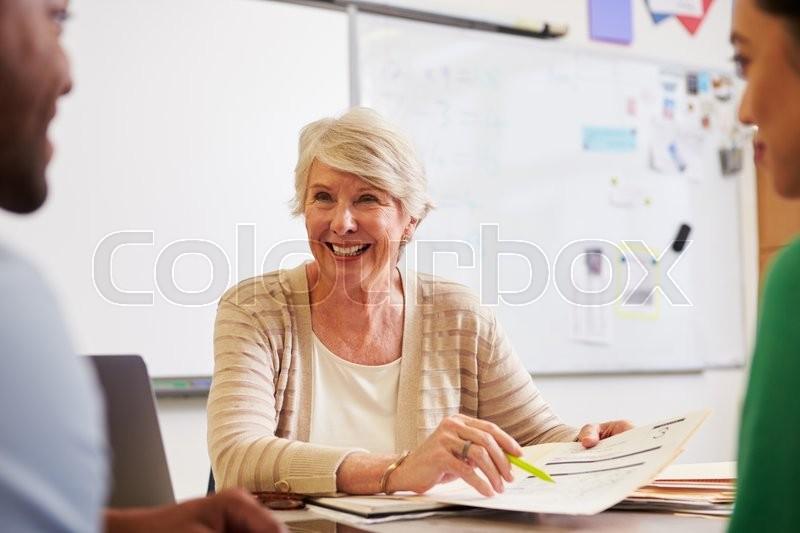 Senior teacher at desk talking to adult education students, stock photo