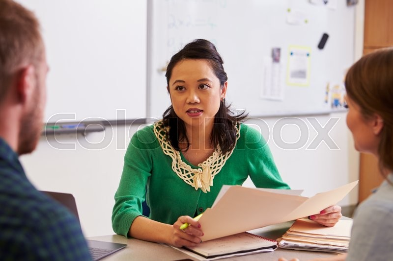 Teacher at desk talking to adult education students, stock photo