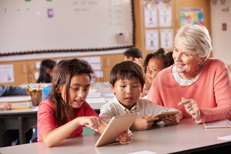 Senior teacher helping elementary school pupils using tablet, stock photo
