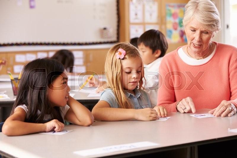 Senior teacher helping pupils in elementary school lesson, stock photo