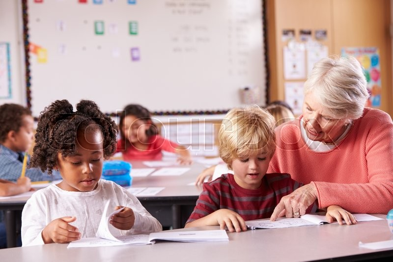 Senior teacher helping elementary school pupil in class, stock photo