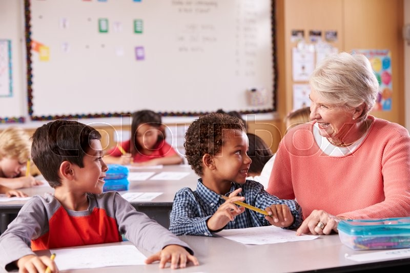 Senior teacher sitting with elementary school kids in class, stock photo