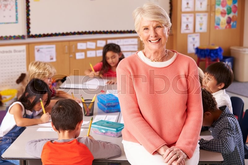 Senior teacher in classroom with elementary school kids, stock photo