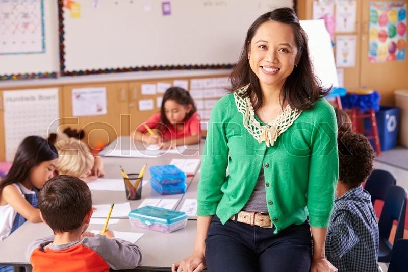 Portrait of teacher in classroom with elementary school kids, stock photo