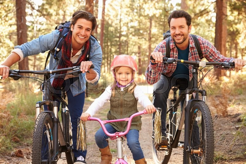 Gay Male Couple With Daughter Cycling Through Fall Woodland, stock photo