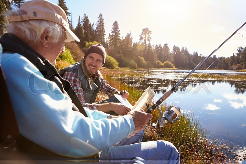 Father and adult son fishing lakeside, close-up, stock photo