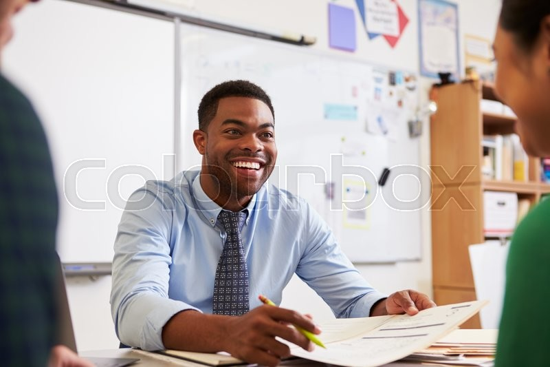 Happy teacher at desk talking to adult education students, stock photo