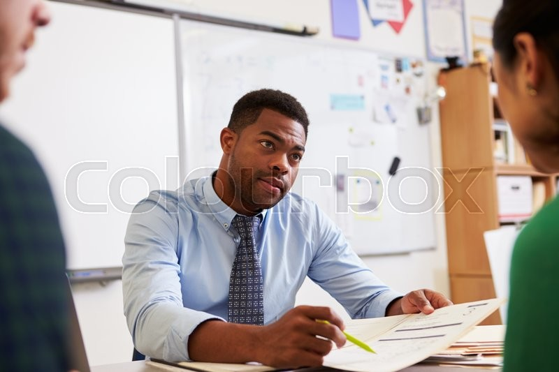 Serious teacher at desk talking to adult education students, stock photo