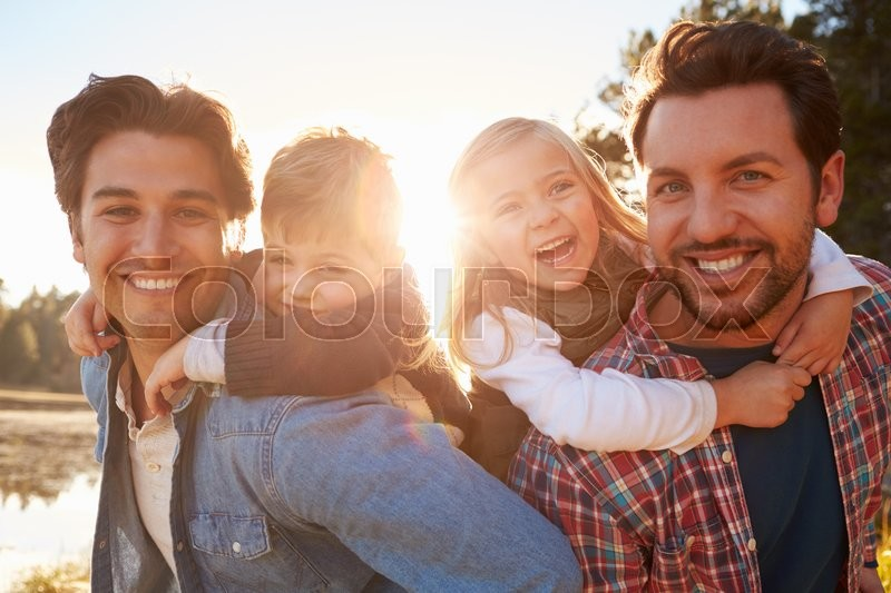Gay Male Couple With Children Walking By Lake, stock photo