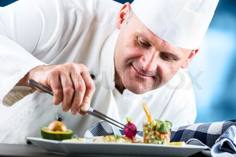 Chef. Chef cooking.Chef decorating dish. Chef preparing a meal. Chef in hotel or restaurant kitchen prepares decorating dish with tweezers. Chef cooking, only hands, stock photo
