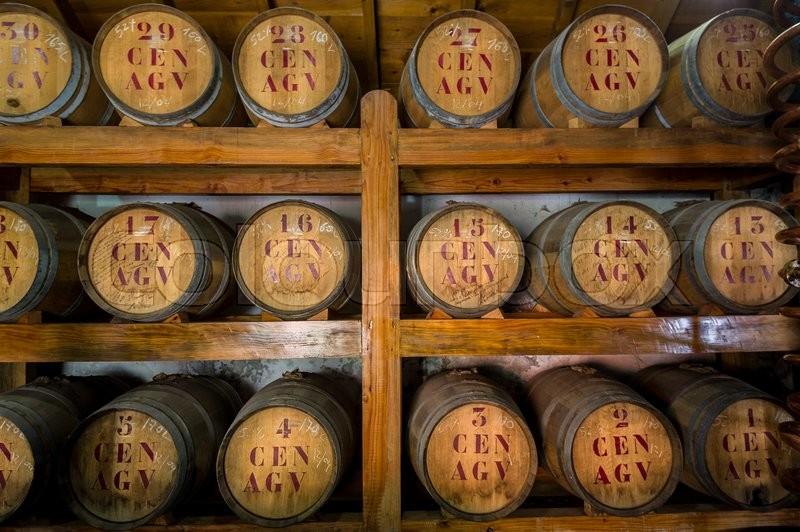 Old wooden wine barrels at storage room. Rum museum of Porto da Cruz, Madeira island, Portugal, stock photo