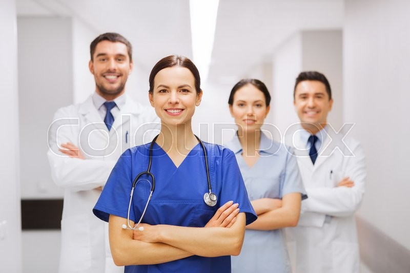 Clinic, profession, people, health care and medicine concept - happy group of medics or doctors at hospital corridor, stock photo