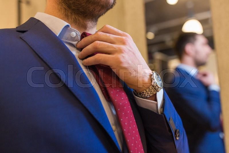 Sale, shopping, fashion, style and people concept - elegant young man choosing and trying tie on at clothing store, stock photo