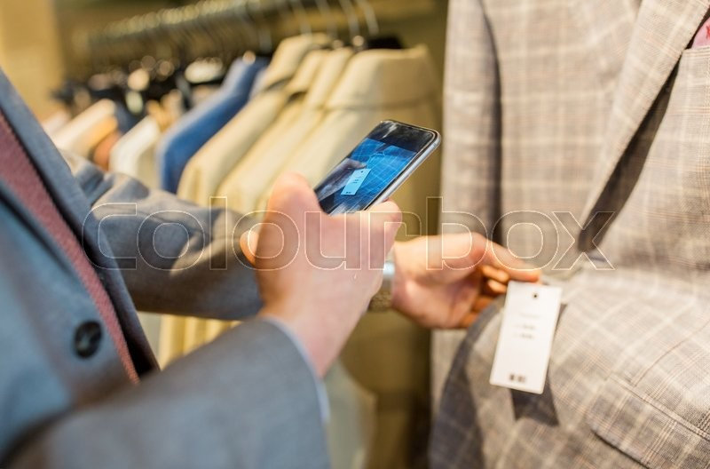 Sale, shopping, fashion, technology and people concept - close up of man in suit with smartphone choosing clothes at clothing store, stock photo