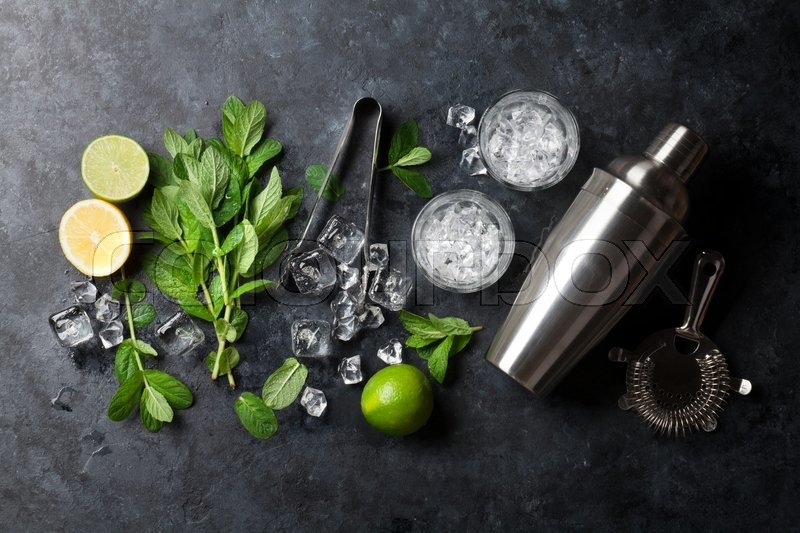 Mojito cocktail making. Mint, lime, ice ingredients and bar utensils. Top view, stock photo
