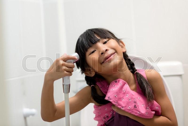 Asian Girl Sitting On Toilet And Using Bidet Stock Photo