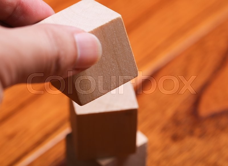 Hand is putting the block onto the block tower with wooden floor background, stock photo