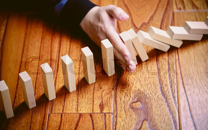 A male hand stopping the domino effect. Risk control and Solution concept, stock photo