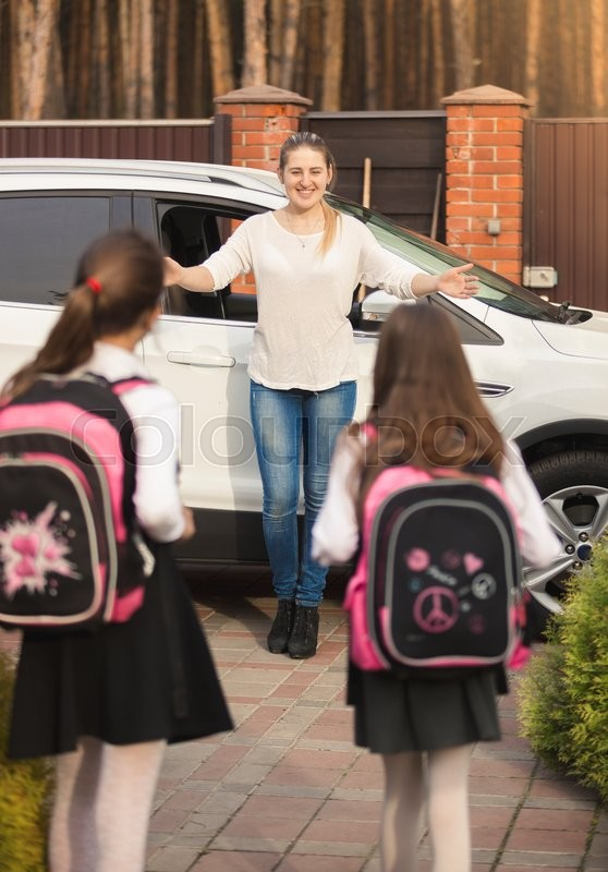 Two cheerful girls running to mother meeting them after school, stock photo