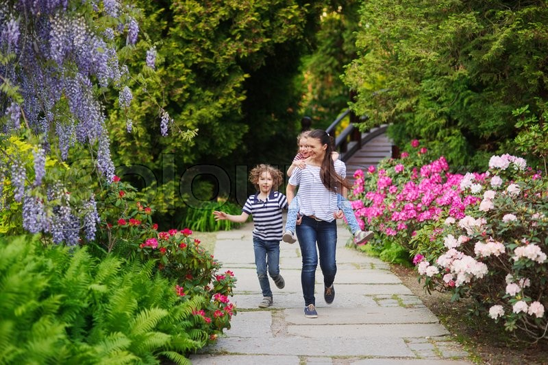 Walk In Garden Box: Mom With Two Kids Walking Along The Alley Blooming Garden