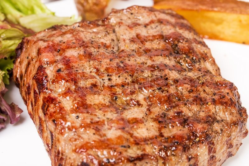 Traditional New York strip steak with potato wedges and fresh lettuce. Macro. Photo can be used as a whole background, stock photo