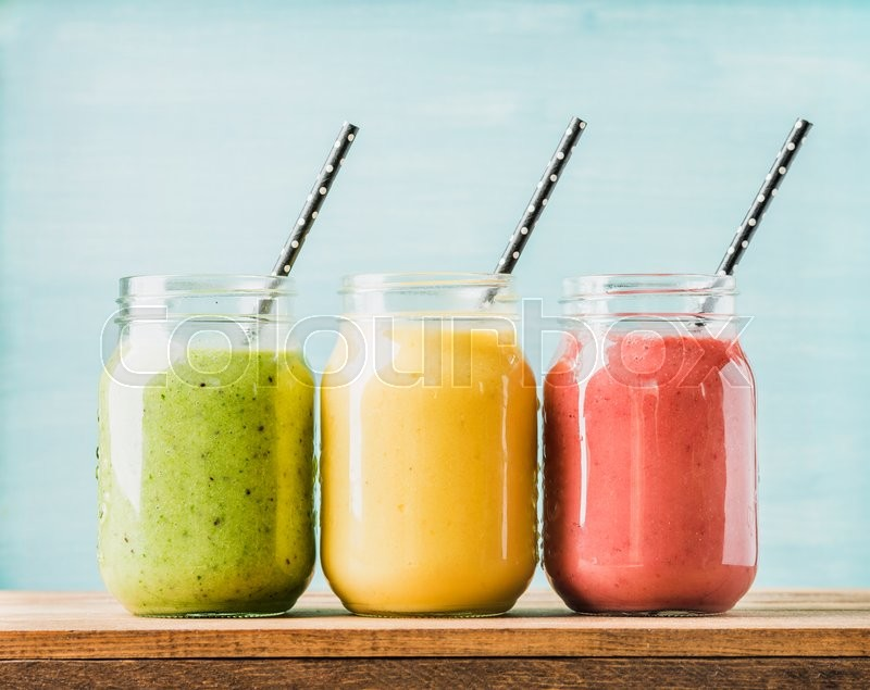Freshly blended fruit smoothies of various colors and tastes in glass jars. Yellow, red, green. Turquoise blue background, stock photo