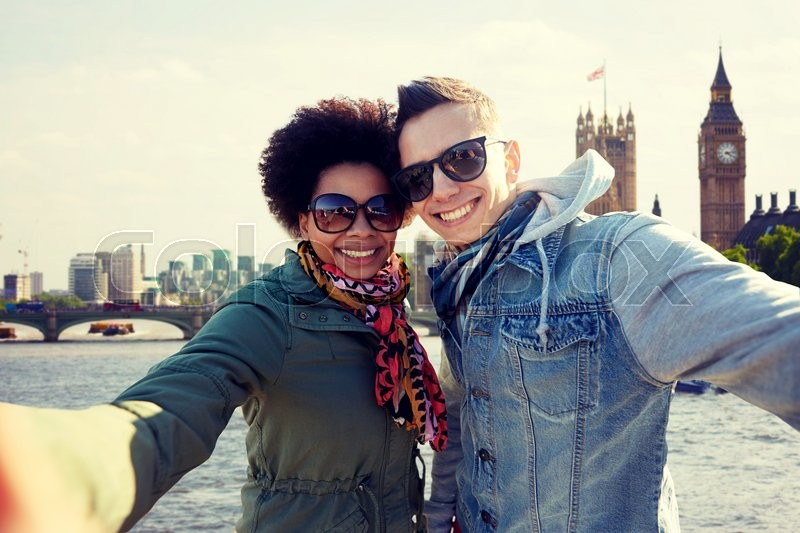 Tourism, travel, people, leisure and technology concept - happy teenage international couple taking selfie over houses of parliament and thames river in london background, stock photo