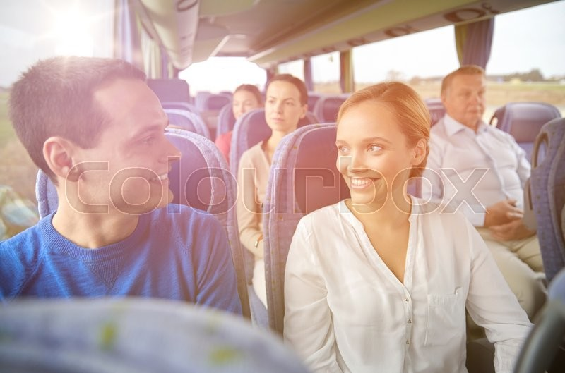 Transport, tourism, road trip and people concept - group of happy passengers or tourists in travel bus, stock photo