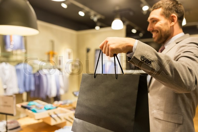 Sale, fashion, retail, business style and people concept - close up of happy man in suit with shopping bags at clothing store, stock photo