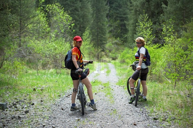 Stock image of 'Two womens on mountain bikes on old road in forest'
