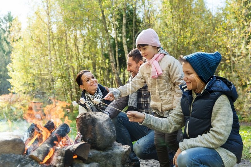 Camping, travel, tourism, hike and people concept - happy family roasting marshmallow over campfire, stock photo