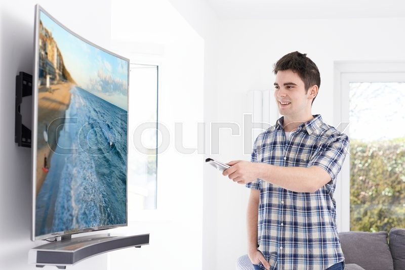 Young Man With New Curved Screen Television At Home, stock photo